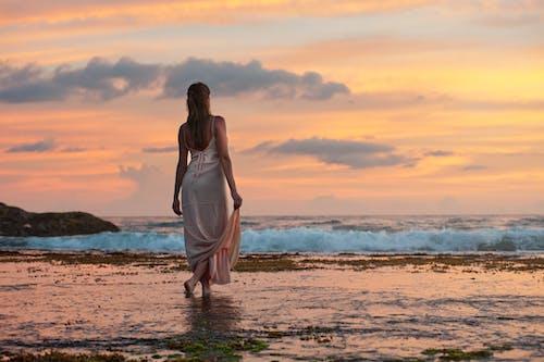 Woman Standing on Sand Near Shoreline