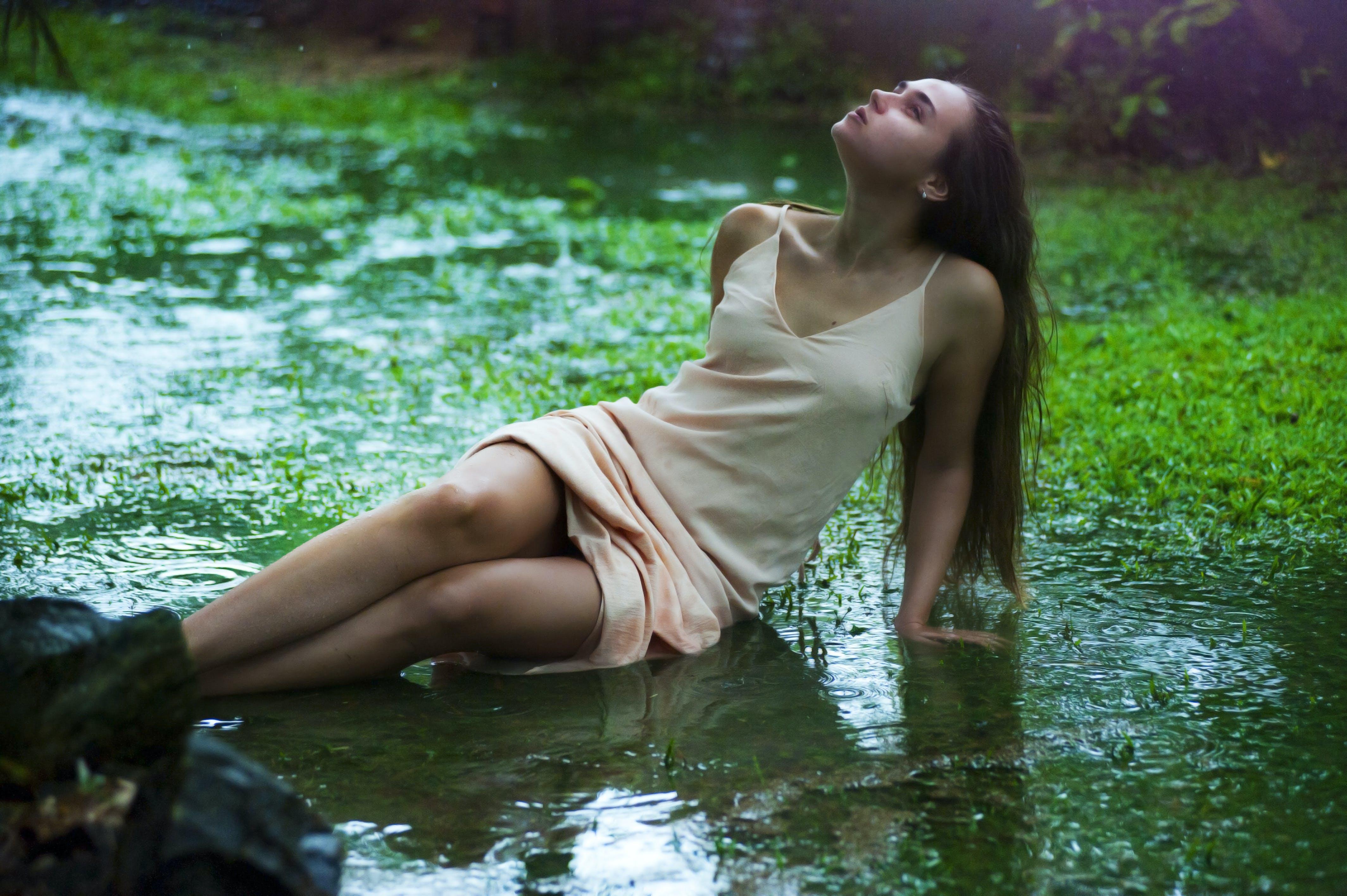 Woman Lying on Wet Grass Field