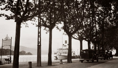 An Old Black And White Photo Of Cars In A Street By The River With A Boat Anchored By The Docks