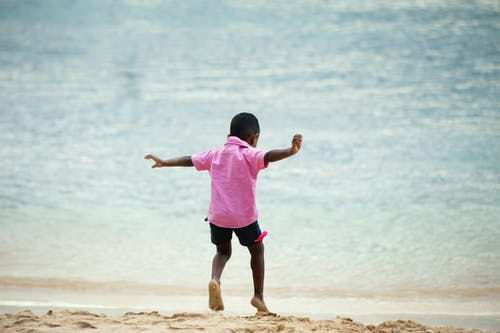 Boy Wearing Pink Collared Shirt Running on Seashore