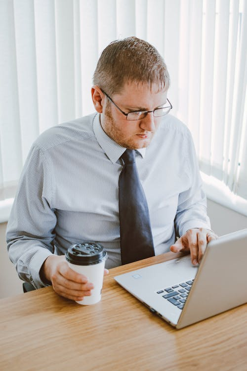 Man in Gray Dress Shirt Holding Coffee Cup and Using Laptop Computer