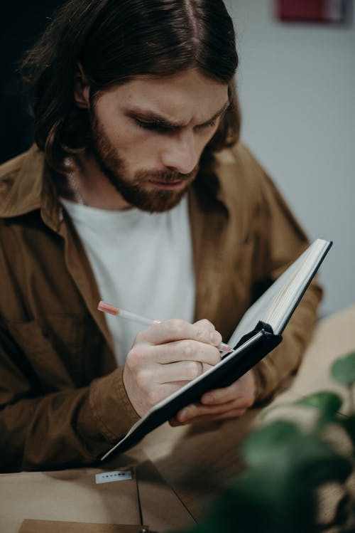 Man Writing on Notebook