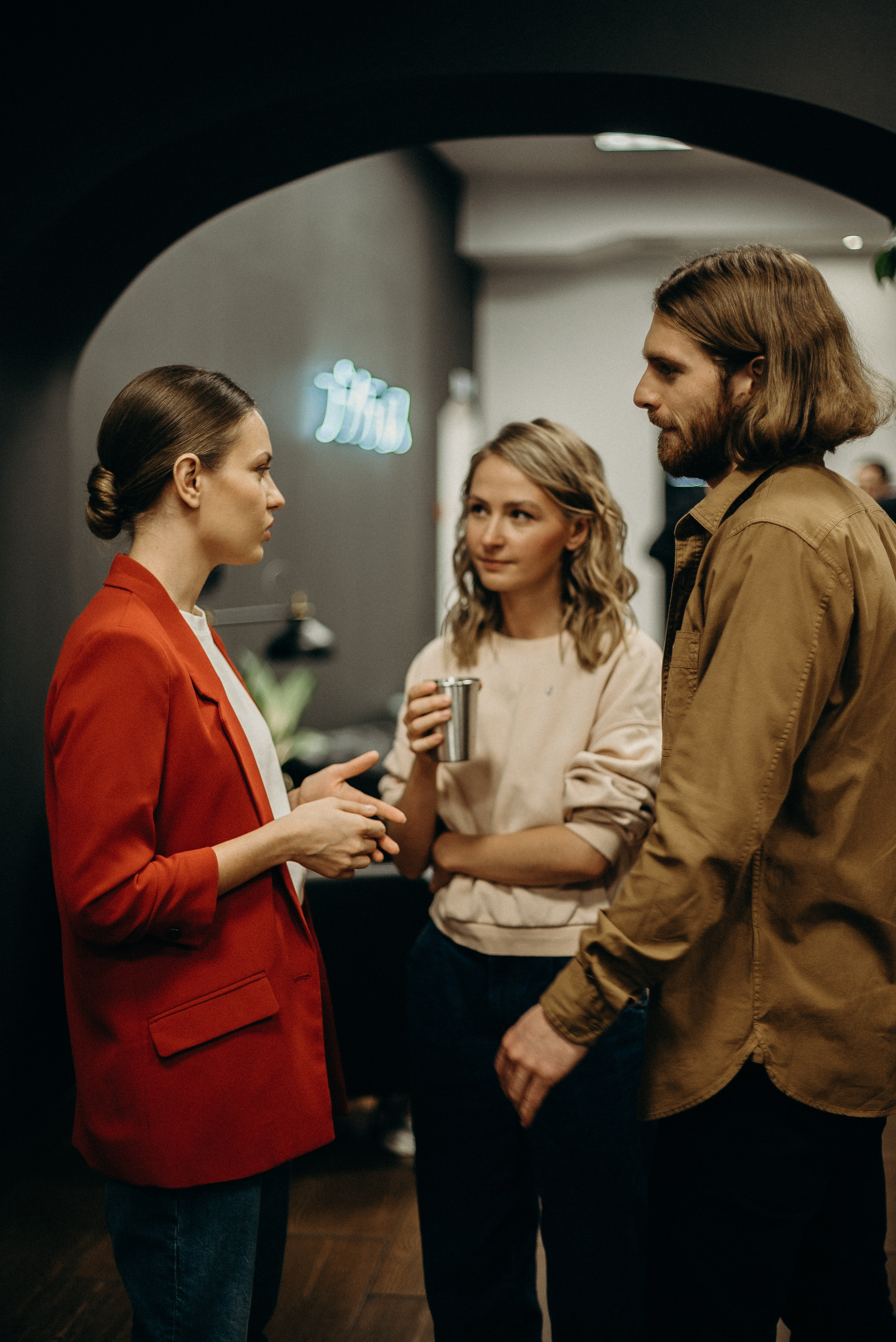 Two women and a man talking. | Photo: Pexels