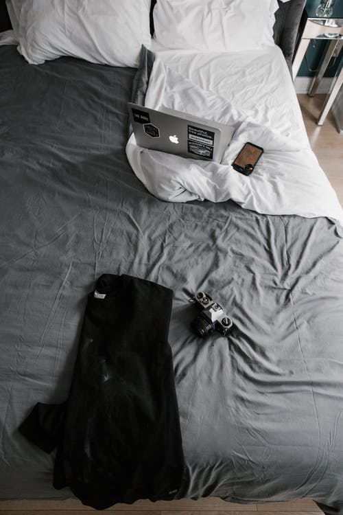 Black Jacket Beside Camera on Bed