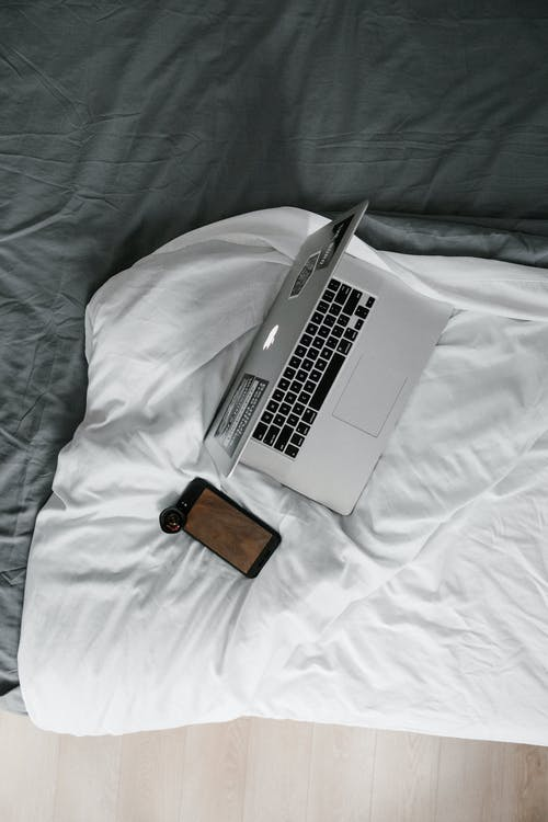 Silver Macbook Pro on White Bed Blanket