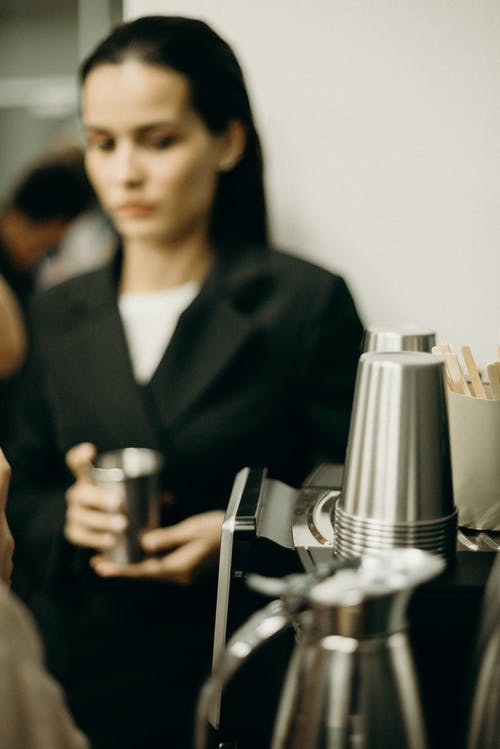 Woman Wearing Black Suit Holding A Stainless Cup