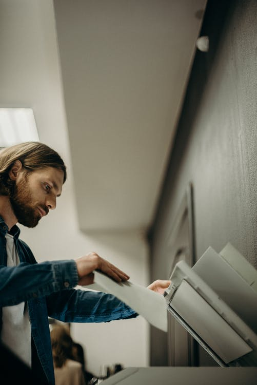 Man in Blue Denim Jacket Holding a Printing Paper