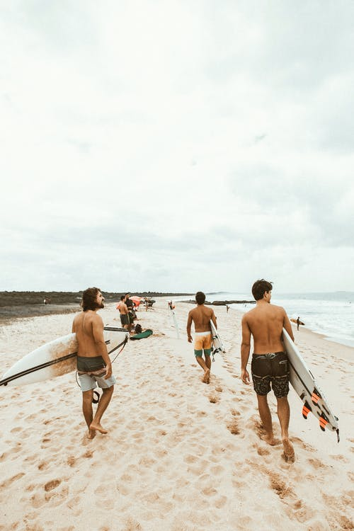 People Holding Surfboards Walking On Shore