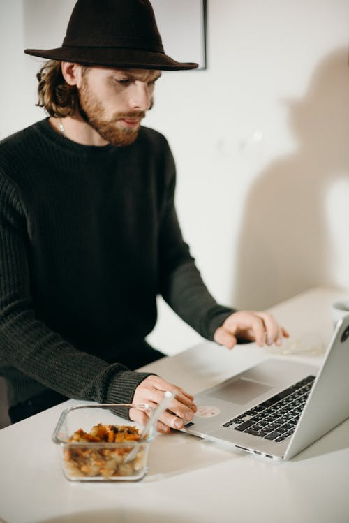Man in Black Sweater Using a Laptop