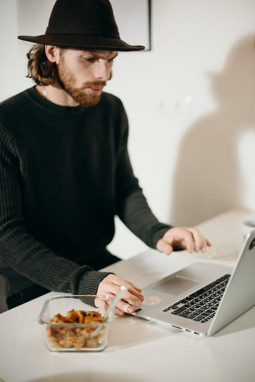 Man in Black Sweater Using a Laptop