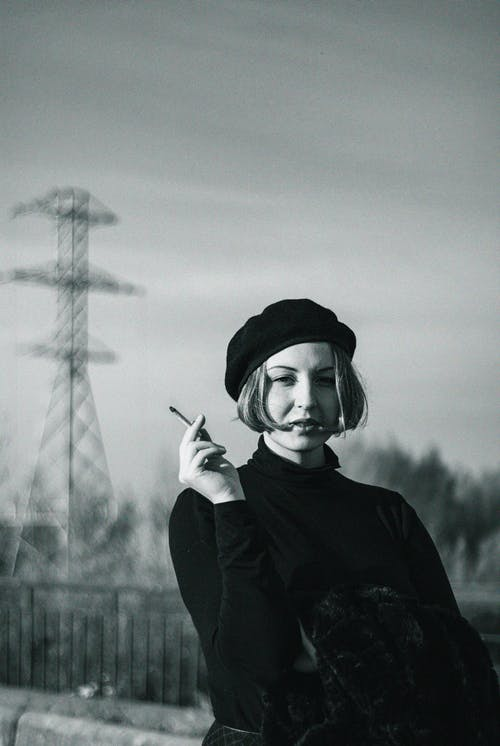 Grayscale Photo of a Woman Holding a Cigar