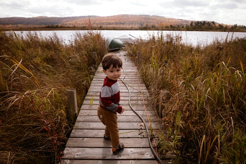 Photo of Boy Standing on Boardwalk