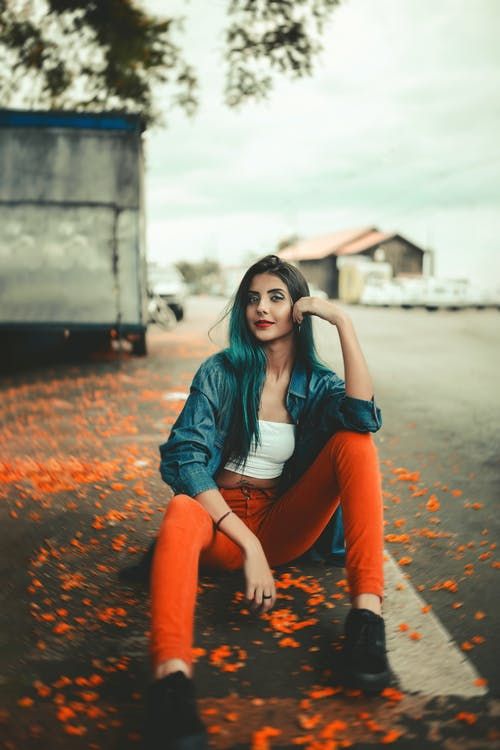 Photo of Woman in Blue Denim Jacket and Orange Pants Posing While Sitting on the Road