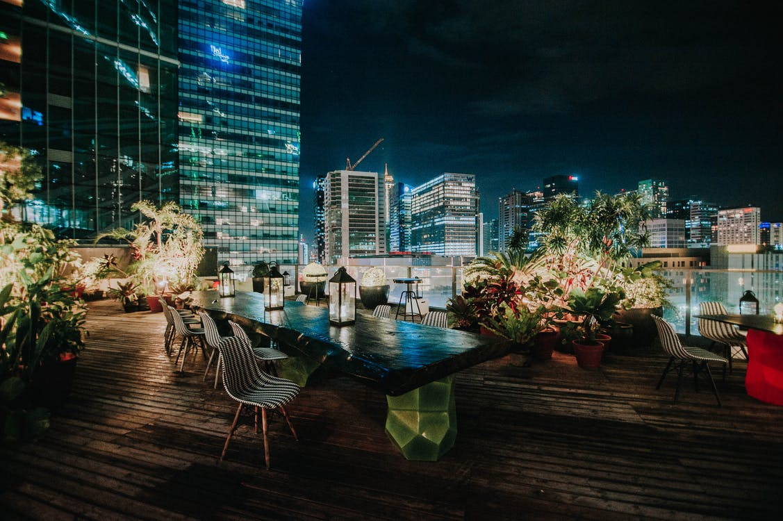 View Of The Cityscape From A Rooftop Garden Restaurant At Night