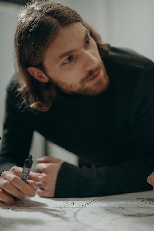 Man in Black Sweater Holding Marker Pen