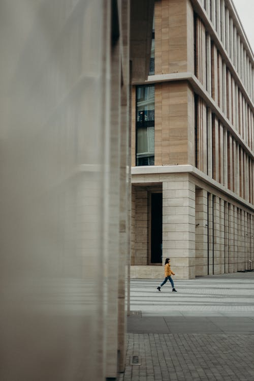 Woman Walking Near Concrete Buildings