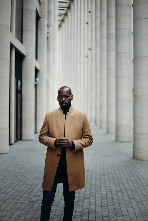 Photo of Man in Brown Coat Posing in the Middle of a Paved Hallway
