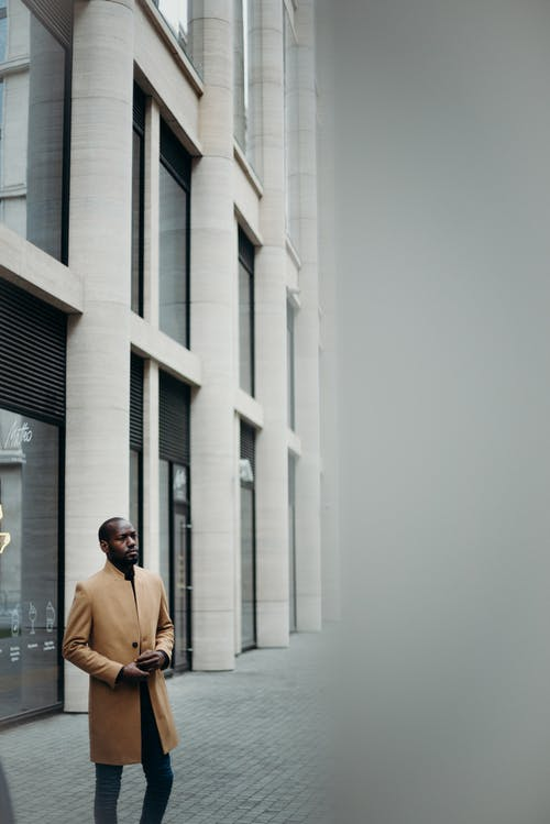 Photo of Man in Brown Coat Posing Outside Building