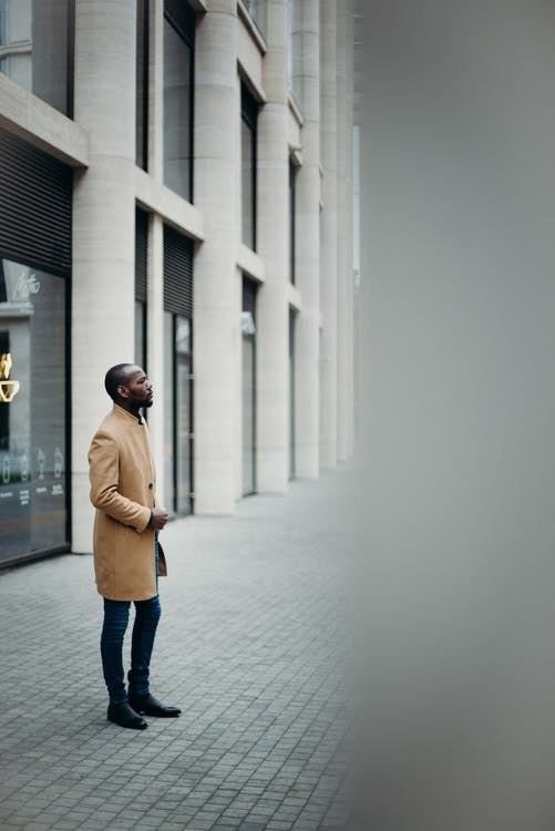 Side View Photo of Man in Brown Coat Posing Outside Building