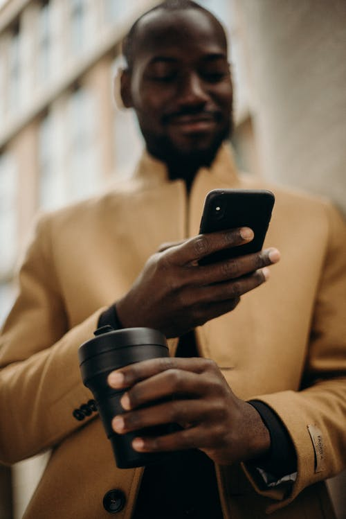 Selective Focus Photo of Smiling Man Looking at His Phone While Holding Cup