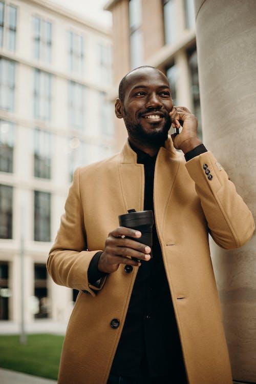 Mann, Der Braune Jacke Unter Verwendung Des Smartphones Während Der Verwendung Des Smartphones Trägt