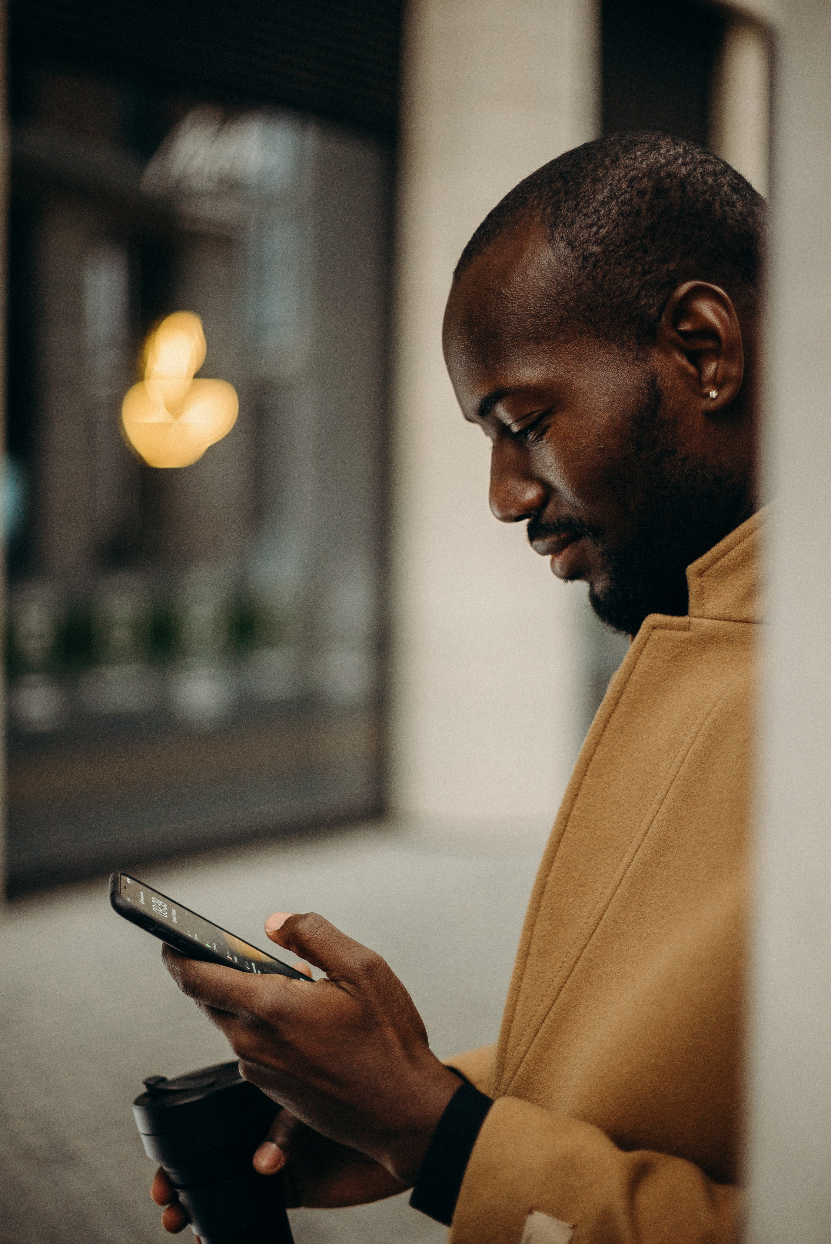 Side View Photo of Man in Brown Coat Using Smartphone While Holding Cup of Coffee