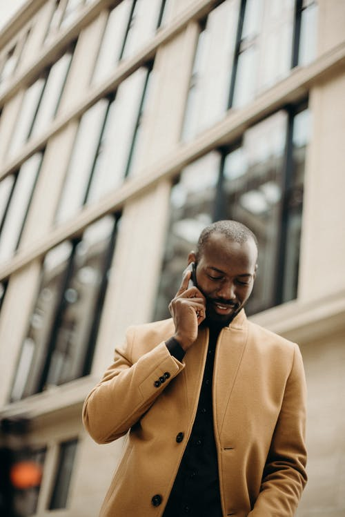 Selective Focus Low Angle Photo of Man in Brown Coat Speaking on Phone wit Building in the Background