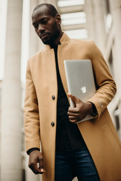 Man Wearing Orange Trench Coat Holding Silver Macbook Pro