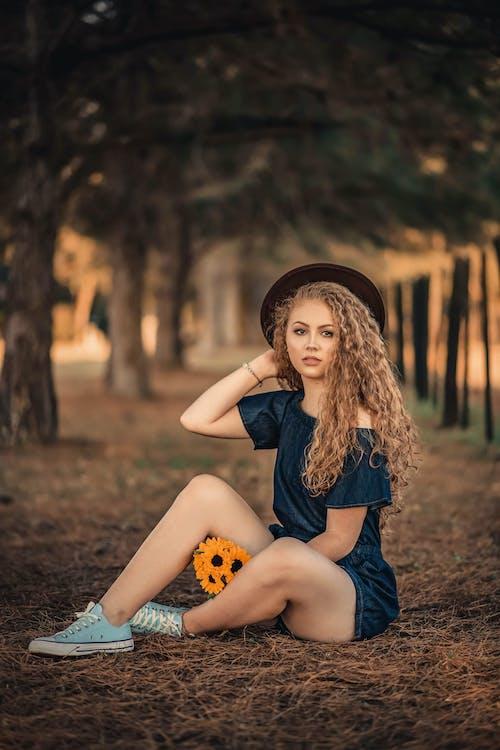 Woman Wearing Blue Off-shoulder Romper Sitting on Ground Holding Orange Flowers
