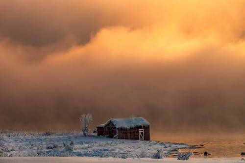 A Brown Barn Close To The River Under Cloudy Skies And Snow Covered Grounds In Winter