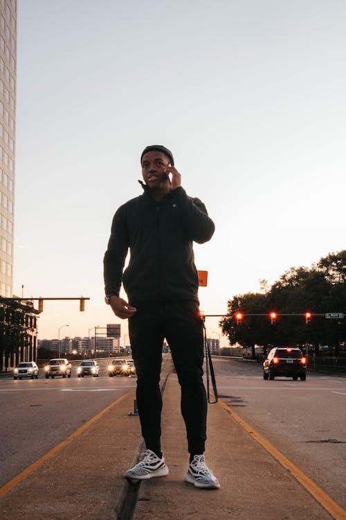 Man Wearing Black Jacket and Black Track Pants Using Smartphone
