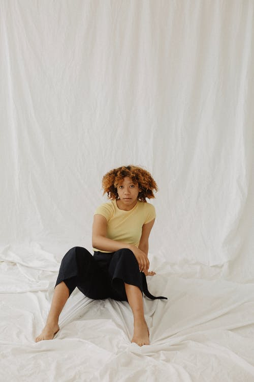 Photo of Woman in Yellow T-shirt and Black Pants Posing while Sitting on White Sheet