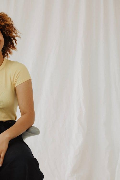 Woman in Beige T-shirt Beside Wall
