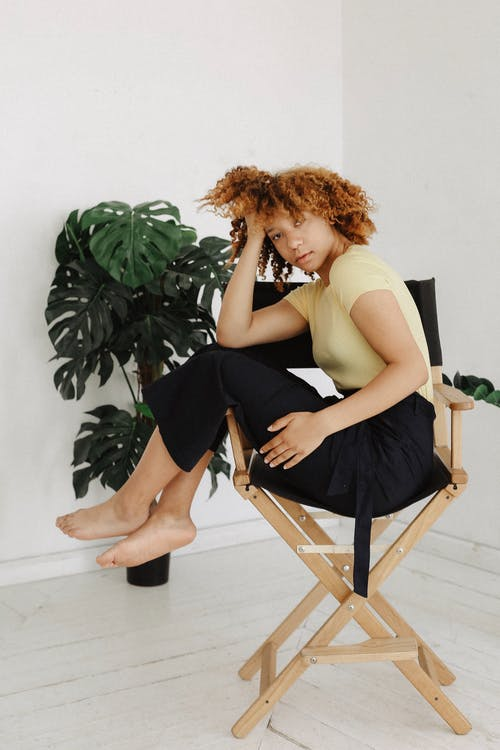 Woman Sitting on Brown and Black Director's Chair