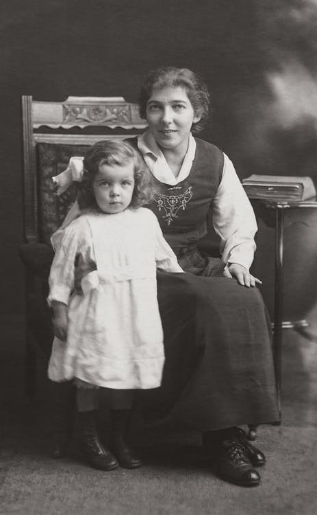 Grayscale Photography of Mother Sitting on Wooden Armchair With Daughter