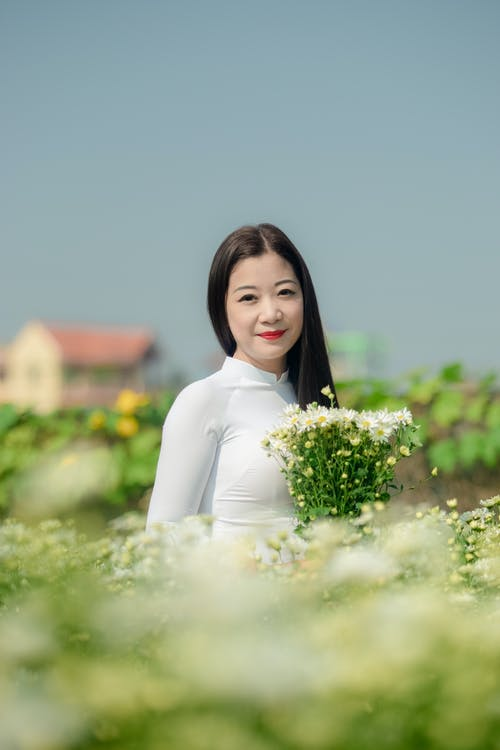 Woman Wearing White Long-sleeved Top Holding White Flowers