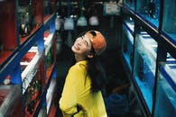Photo of Smiling Woman in Yellow Top and Orange Hat Posing by Fish Tanks