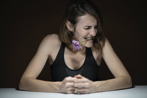 Woman in Black Tank Top Biting Purple Petaled Flower