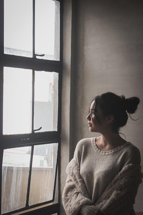 Woman Wearing White Sweater Standing Beside Window