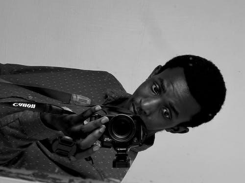 Foto profissional grátis de um homem de câmera segurando a câmera na frente do espelho