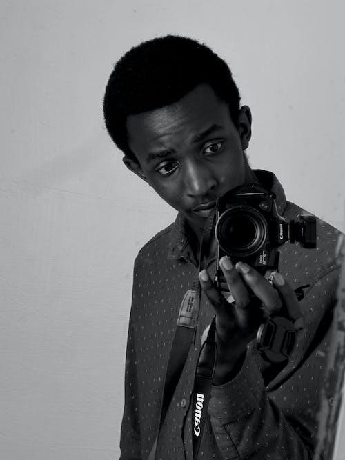 Foto profissional grátis de um homem segurando a câmera na frente de um espelho sujo