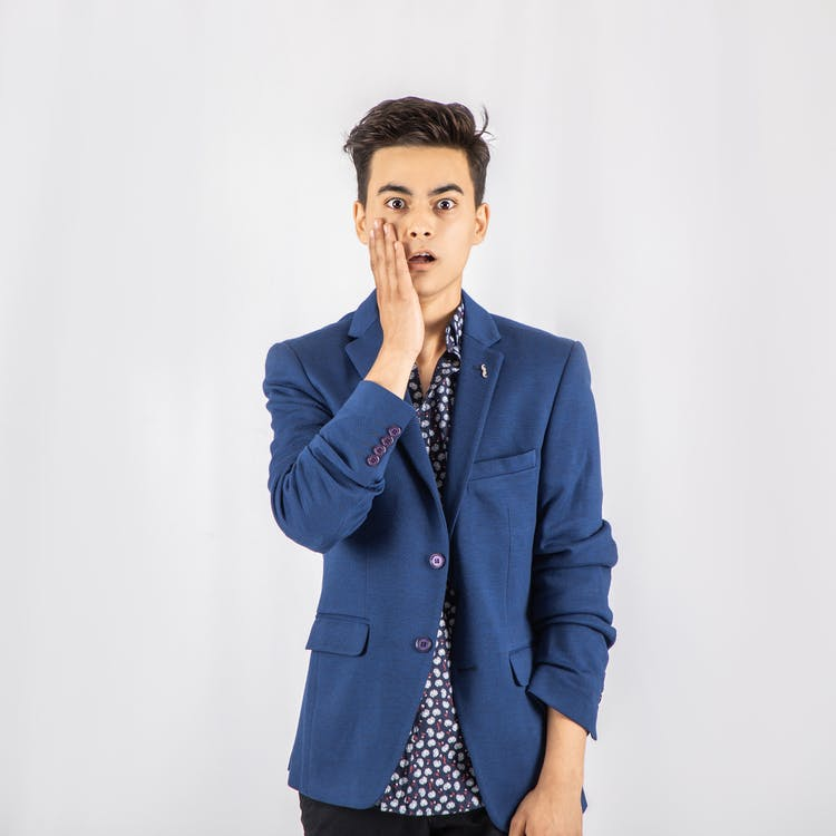 Photo of Shocked Man in Blue Blazer Standing In Front of White Background