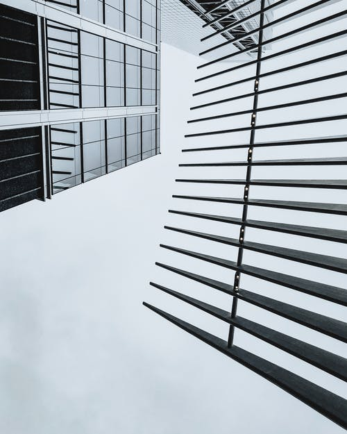 Low Angle Shot Of a Black And White Modern Building With Glass Exterior And Iron Fence