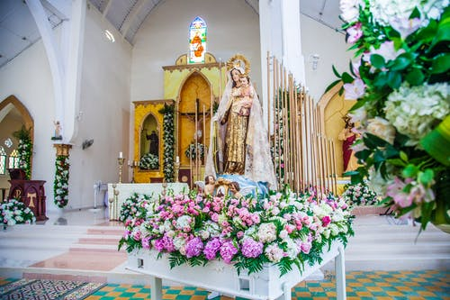 Statue Of The Mother And Child Surrounded With Flowers Close To The Church Altar