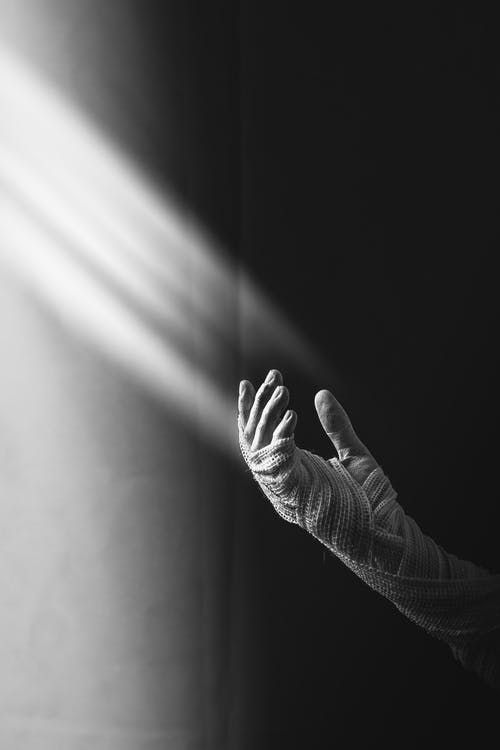 Grayscale Photography of Person's Hand Covered With Straps