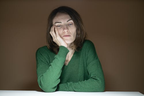 Woman in Green Sweater Holding Her Cheek