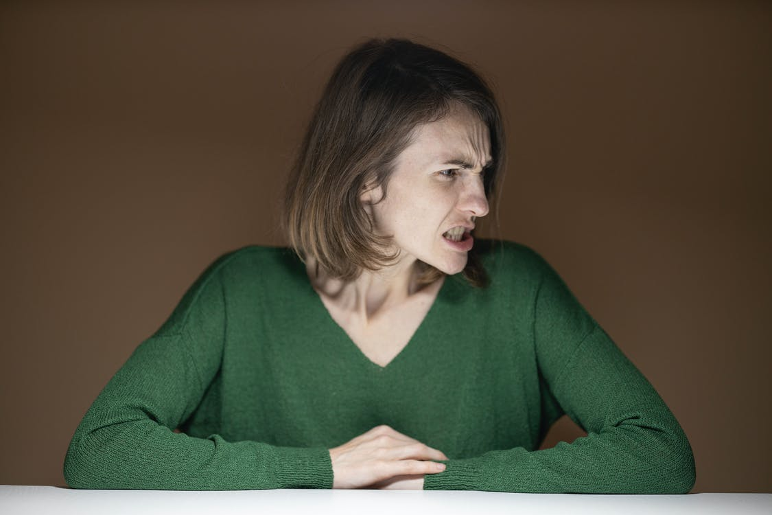Woman in Green V-neck Sweater Leaning on Table