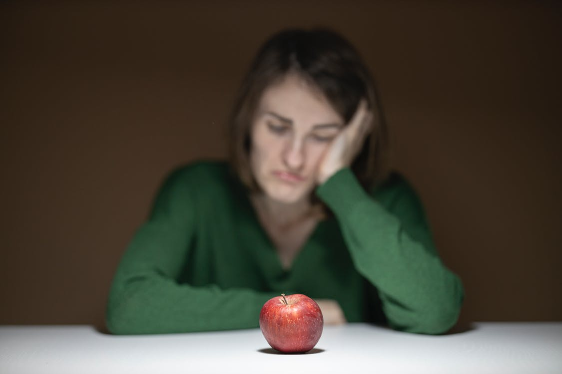 Woman in Green Sweater Sitting in Front of Apple