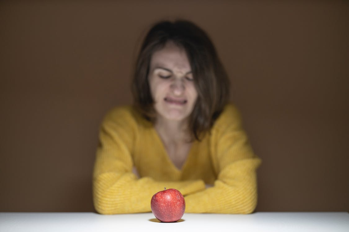 Woman Disgusted Looking at the Apple