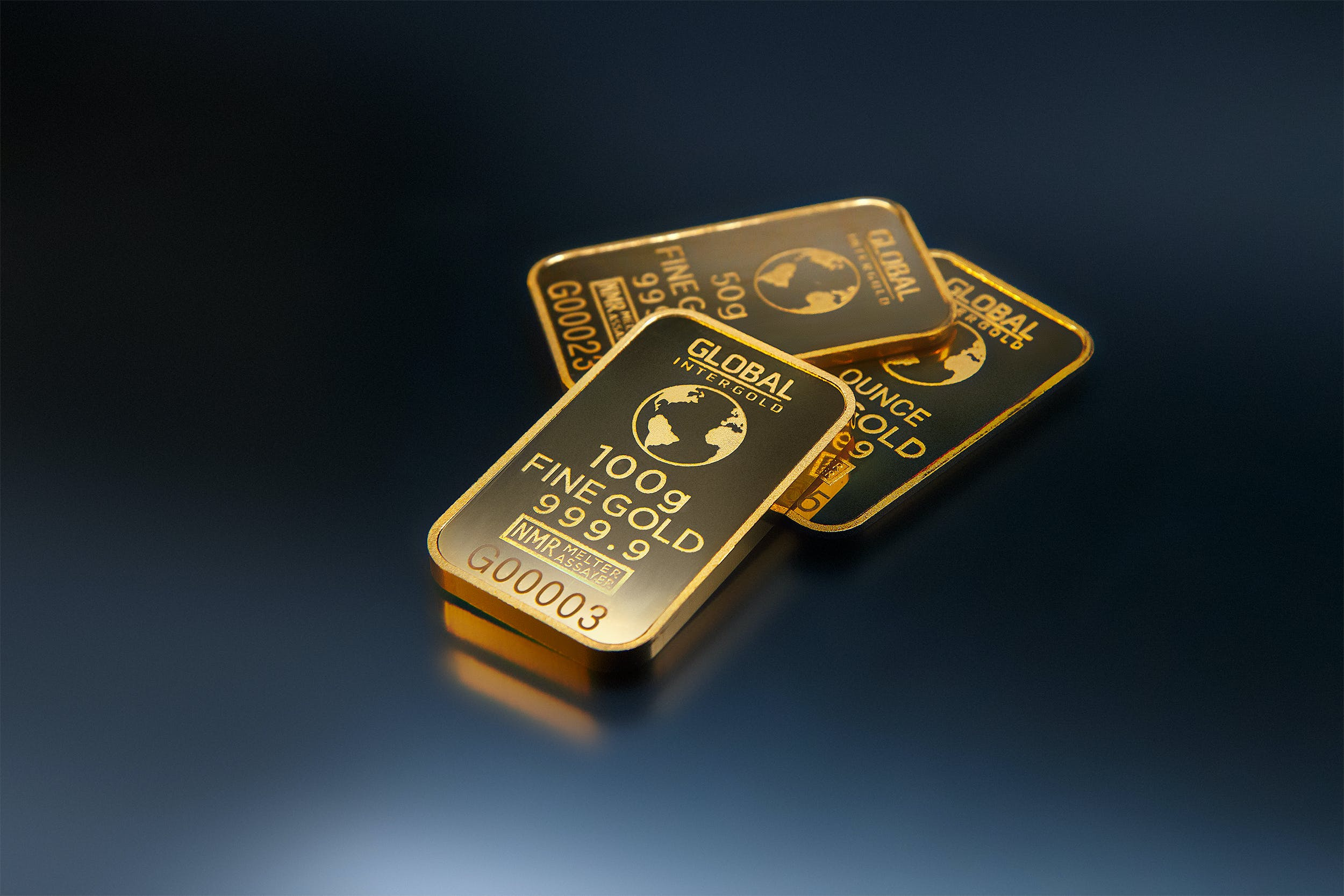 Three Gold Bars Against Dark Background